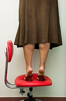 A female office worker standing dangerously on an office chair