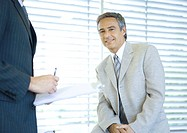 Businessman smiling at camera while colleague signs document (thumbnail)