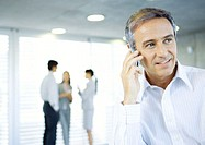 Mature businessman using cell phone, colleagues talking in background