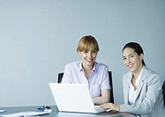 Two businesswomen using laptop, smiling at camera