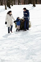 Family outside with Christmas tree