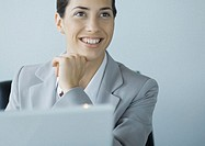 Businesswoman looking up from laptop
