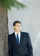 Businessman leaning against tree, portrait