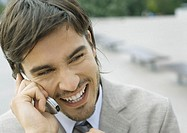 Young businessman using cell phone and laughing