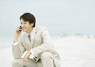 Businessman crouching on beach, using cell phone