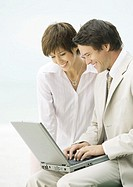 Businessman and woman using laptop together