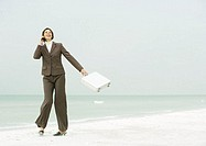 Businesswoman using cell phone and swinging briefcase on beach