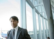 Businessman by window in airport (thumbnail)