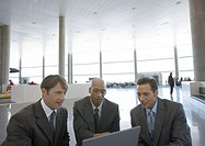 Three businessmen using laptop in airport