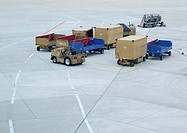 Luggage trucks and oontainers on airport runway