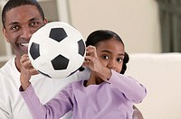 Father with daughter holding soccerball