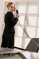 Businesswoman holding telephone, portrait.