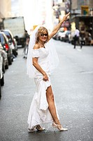 Bride hailing taxi in wedding dress in the middle of street