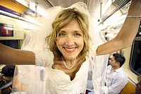 Bride in wedding dress in subway car smiling in camera