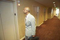 Side profile of a businessman holding his bag and standing in front of an elevator