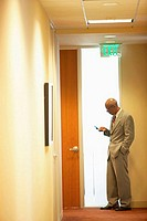 Side profile of a businessman operating a mobile phone