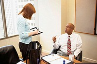 Businessman talking to his secretary in an office
