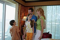 Young couple standing with their son and daughter in a hotel room