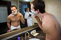 Reflection of a young man shaving in a mirror