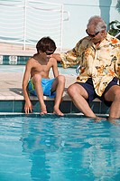 Senior man sitting with his grandson at poolside
