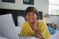 Portrait of a boy lying in the bed in front of a laptop and smiling