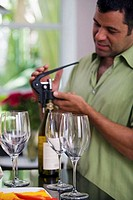 Side profile of a mature man unscrewing the cork of a wine bottle
