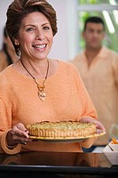 Portrait of a mature woman holding a pie
