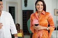 Portrait of a mid adult woman standing with a mid adult man holding wineglasses