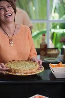 Close-up of a mature woman holding a pie