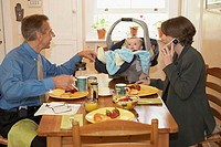 Side profile of a mid adult couple with their son at a dining table