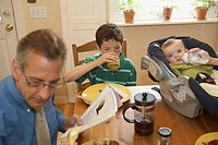 High angle view of a mid adult man with his two sons sitting at a dining table (thumbnail)