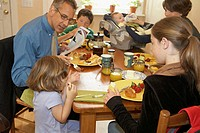 Mid adult couple having breakfast with their two daughters and two sons
