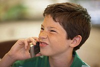 Close-up of a boy using a mobile phone and making a face