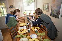 Side profile of a mid adult woman and her daughter cuddling a baby boy at a dining table