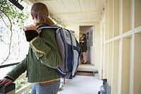 Side profile of a teenage girl going to school with her mother standing at the door