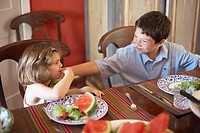 High angle view of a boy and his sister sitting at a dining table and looking at each other