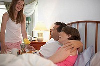 Side profile of a mid adult couple in the bed with their daughter holding a tray standing beside the bed