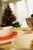 Close-up of bowls and plates on a table with a Christmas tree in the background