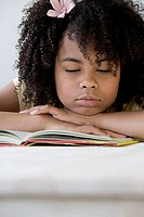 Close-up of a girl sleeping on a book
