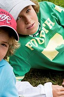 Portrait of two boys reclining on grass