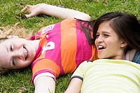 High angle view of two girls lying on the grass and smiling