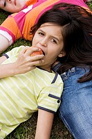 Portrait of a girl eating an apple with her head resting on another girl