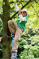 Portrait of a boy climbing a tree