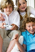 Close-up of a boy playing a video game with his friends