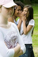 Close-up of a girl looking serious with two girls laughing behind her