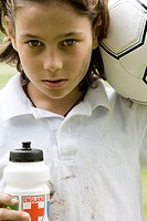 Portrait of a boy holding a soccer ball and a water bottle