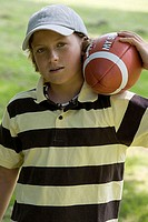Portrait of a boy carrying a football on his shoulder