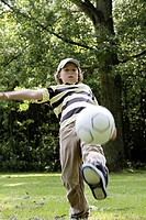 Boy playing with a soccer ball in a field