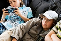 Portrait of a boy lying on the bed with another boy playing a handheld video game beside him
