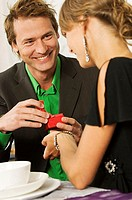 Close-up of a mid adult man giving a Christmas present to a young woman